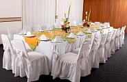 Оформление стульев в белом цвете и цветочные композиции на столе