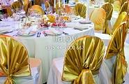 Украшение свадебного зала в бело-золотом цвете. Стулья украшены золотыми получехлами одетыми на полный белый чехол