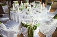 Изумрудные банты навязаны на полный белый чехол. Стол декорируется с использование атрибутов изумрудного цвета (карточки рассадки, свечи, цветы и вазы, другое)